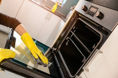 hands in yellow protective rubber gloves cleaning oven