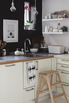 A small black and white kitchen, with a great mix of wood tones that doesn't create any visual clutter