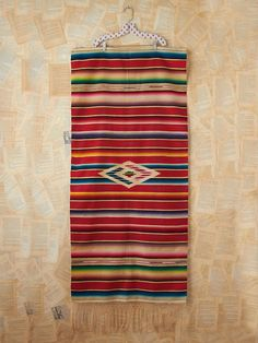 Vintage Mexican serape blanket with vibrant colors and a fringed hem.
