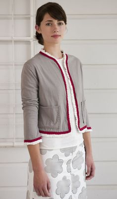 Ruffle Hem Jacket  This hand-sewn garment is made from 100% organic cotton. The pleated trim and front pockets add delicate details to this jacket for a truly feminine feel. Shown here in Silt with Carmine and White.