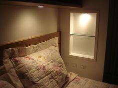 Prateleira lateral e luz embutida em cima da cama.
