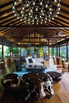 The open-air lobby of @Mandy Dewey Seasons Resort Seychelles features a dazzling array of modern and natural design elements, including gnarled wood and a chandelier of exposed lightbulbs.