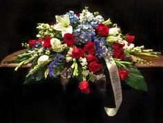 casket piece of red and white roses, blue hydrangeas, larkspur, gladiolas, and white lilies