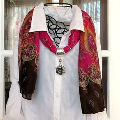 Fun gauzy scarf in primarily pink and brown with a transition of multi colored patterns. The pendant is a 3-D flower. This scarf is made of polyester and is 68 inches long.