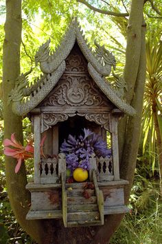 A spirit house with offerings from the garden.