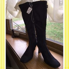 Black high heel boots Man made materials.  Suede like.  Never worn.  Pix show all details..  The calf features a adjustable gusset highlighted by a strap and buckle.  Excellent condition. Very stylish for an inexpensive boot. Expressions Shoes Heeled Boots