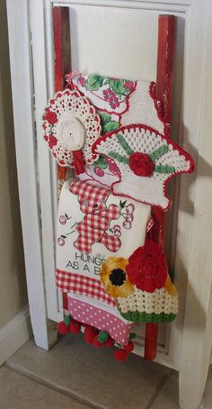 A display of mine (from years back) that was a doll ladder and draped over it vintage pot holders and a towel.