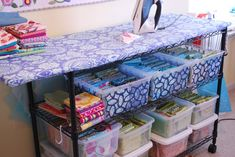 "How to create the Fabric Storage / Ironing Station:    Materials Needed:   * Small Wire Shelving Unit ( ranging from 30"" - 36"" depending on your height & preference)( Home Depot,  WalMart, Target )  * 20x60 piece of 3/4"" MDF board OR OSB Subfloor   * Batting  * Fabric  *Stapler  *S-Hooks & Basket to hang ironing accessories (water spray bottle and starch)"