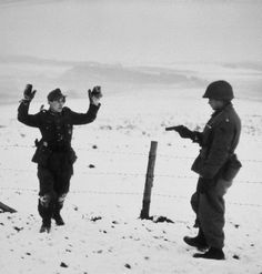 A German soldier surrenders to an American at gunpoint. Ardennes, 1944. Robert Capa
