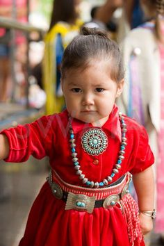 Too cute! She clearly knows how to accessorize with a necklace, concho belt, and pendant. And she's not afraid to use color!