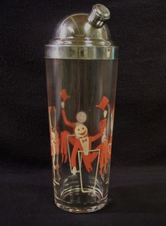 UNIQUE 1950s Mid Century Glass Cocktail Shaker with metal top. Shaker is decorated with painted on Mr. & Mrs. Retro Party, him in his top hat and tail and her in strapless dress and heels. They are both resting in cocktail glasses.