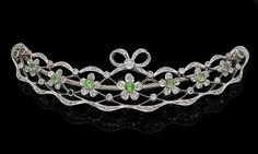 A demantoid garnet and diamond brooch, circa 1905 The crescent-shaped openwork plaque of floral and ribbon design, set throughout with old brilliant and rose-cut diamonds, each flowerhead set with a circular-cut demantoid garnet, length 7.1cm