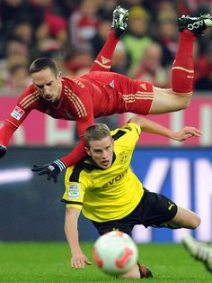 Der Dortmunder Mittelfeld-Abräumer Sven Bender (unten) grätscht den französischen Edeltechniker des FC Bayern Franck Ribery um. (Foto: Tobias Hase/dpa)