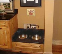 Dog food and water station in a kitchen or utility room.
