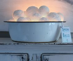 Homemade snowballs and string of lights in the bottom of an old enamel tub.