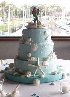 This three tiered beach inspired wedding cake is topped off with Price Eric and Ariel from Disney's The Little Mermaid. White chocolate starfish and seashells adorn the sides.
