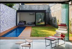 In fondo al piccolo giardino è stato collocato un cubo vetrato, che ospita un ulteriore living, dove rilassarsi e godere dell'apertura sull'esterno