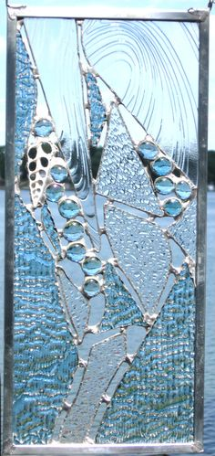 Beachy stained glass panel made of blue/clear textured iridescent glass, seashell, and gems uniquely soldered together to give lacy look.