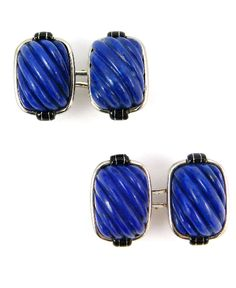 Pair of Art Deco carved cushion shaped lapis lazuli cufflinks, c.1925, each panel formed by a spiral fluted domed lapis, black enamel detail to top and bottom of the polished collet frame, close set and mounted in white gold.