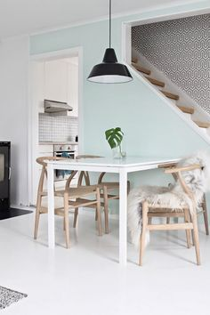 There's so much to love here, from the Hans J. Wegner wishbone chairs to the industrial pendant lamp, all set off by that fresh accent wall against the stairs. This shade is slightly pastel...