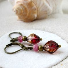 This listing is for a pair of glass beaded dangle earrings from the pink series. These earrings are available in both hypoallergenic, pure titanium ear wire, or you can purchase them as shown, with antique brass wire. The titanium wire will be the same color as the wire shown. This large bead is a 8 x 10mm Czech glass bead. It has a subtle metallic finish and cut grooves along the edges of the bead. These are stunning beads. Each one is slightly different. Some have a bit more clear glass…