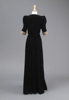 Rear view of full length dress with gathered panel at back. 1930-32 by Madame Clapham Black Velvet Evening Dress 1930-32  The evening dress of black velvet has a ruched sweetheart neckline and an intricately cut bodice. The dress has a high front with elbow length sleeves.  It is fastened with four buttons. The simple but striking decoration found on the cuffs and waistband, is gold lame, with plastic gemstones. The full length dress has a low v-neck and a gathered panel at the back.
