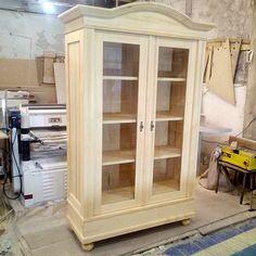 Такой шкаф-витрина будет находкой для адептов классического стиля и всех, кому близко понятие элегантность. Шкаф – вместительный, состоит из четырех полок за стеклянными дверьми. Материал изготовления – натуральное дерево – массив сосны.