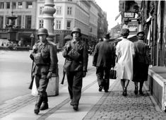 German troops pass Danish civilians on the streets of Copenhagen the day German authorities declared martial law in the country. Since the German occupation of Denmark on 9 April 1940, German authorities found the majority of Danes to be exceedingly uncooperative. After the Danes scuttled several warships in the harbor and six other ships escaped to Sweden, an additional 3,000 German troops were sent to Denmark causing civilians to riot.