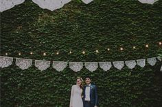 Brooklyn wedding reception in a restaurant's dining courtyard. Ivy wall, globe lights, and papel picado (mexican papercut banners) made by: aymujershop.com /// Photo: Chellise Michael Photography /// https://www.aymujershop.com/collections/weddings/products/lasflores