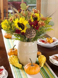 Enhance a crock-contained autumn bouquet with complementary fare arranged around its base. Here, a green-and-yellow-striped runner and yellow and orange gourds highlight the sunflowers, seedpods, wheat and other goodies gathered in the crock.