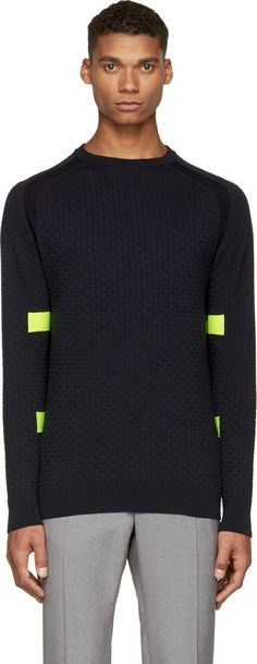 Long sleeve textured-knit sweater in navy blue. Ribbed crewneck collar, cuffs, and hem. Contrasting stitch at raglan sleeve seems and at acid green accent stripes. Tonal stitching.