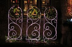 summer Flower trellises decorated with candy cane rope light and christmas wreathes ~ perfect for Christmas lawn decorations