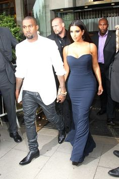 Kim Kardashian Kim Kardashian puts her curves on display in a tight blue dress as she leaves her hotel with her boyfriend Kayne West.