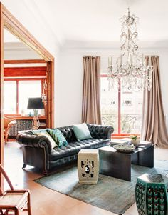 Living room with white walls, black leather couch, blue rug, assortment of coffee tables, blue throw pillows, beige curtains, and large crystal chandelier