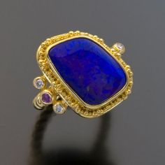 Ring | Zaffiro Jewelry  Ring is set with an Australian Boulder Opal (7.44cts), a Violet Sapphire (.07cts) and Diamonds (.12tcw) in granulated 22kt yellow gold with an 18kt yellow gold band. Overall length: .875""