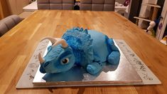 Home made triceratops birthday cake  Body is vanilla sponge baked in a pyrex bowl. Head and Head Plate made with rice krispie and marshmallow mixture for modelling.  Fondant icing and food colouring to finish.   Texture on skin made with impressions from varioud washed pen lids