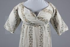 A printed muslin day dress, circa 1800-1810, self-striped and printed with foliate bands in shades of buff and blue, with apron-fall to bodice and skirt front, the bodice held in place by buttons and loops, empire line linen inner-bodice panels with draw-string, button fastened waistband, bust approx 28in, 71cm This dress has been on display at the Jane Austen museum over the last decade.