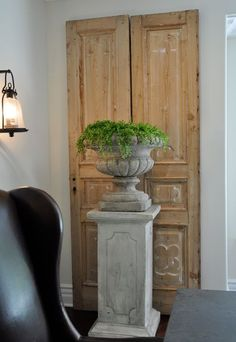On top of their pedestals, these planters are the perfect mid-level height elements in the dining room. By Giannetti home Design.