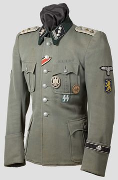 Field tunic of an SS-Hauptsturmführer from the 14. Waffen Grenadier Division der SS Galicia (ukrainische Nr 1). It belonged to a German officer who served in the Totenkopf Division, hence the SS-Totenkopfstandarte Oberbayern cuffband, and was transferred to Galicia Division to boost experience in the officer corps. Note the machine-embroidered rampant lion collar patch and the Galician arm shield, with golden-yellow rampant lion, crowns and border on a blue field.