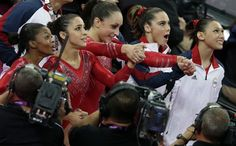 The U.S. Gymnasts react as they watch the screen that displays results declaring them winners of the gold medal the the women's team final. Credit: AP Photo/Gregory Bull