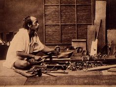 A Japanese woodworker uses the traditional tools of his trade in a photograph taken in the early years of the Meiji era (1868–1912).