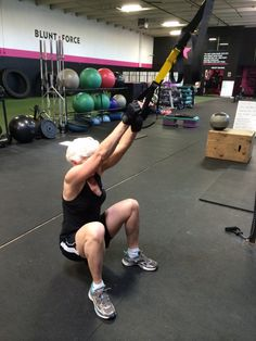 Squat to a row using the TRX band.
