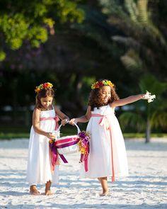 flower girls sprinkle fresh flower petals down a sandy aisle