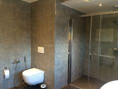 Vegghengt #toalett og stor #dusj med #skyvedører i glass.