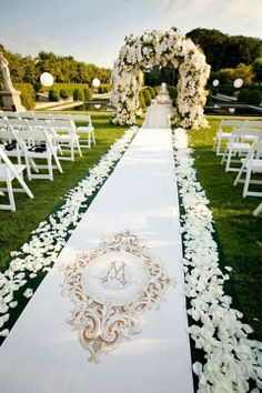 Stunning out ceremony set up with a beautifully decorated white floral arch at the altar, and white rose pedals along a monogrammed runner. Aisle pews? Rose gold or champagne colored harps.