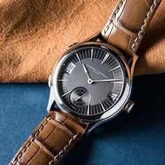 The slate grey dial of this Laurent Ferrier Galet Traveller has two contrasting finishes: a vertical satin-brushed finish in the centre and a circular satin-brushed around the outside. :