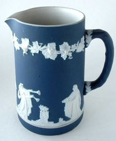 This is a Victorian antique Adams, England victorian jasper ware pitcher or jug in a dark blue dip with classical applied relief figures like Wedgwood's Sacrifice Figures. The pitcher or jug measures