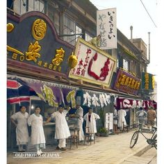 Japan. Tokyo. Sidewalk Restaurants. (May 1934). Employees pose in front of Tokyo sidewalk restaurants on a sunny day in May, 1934. The delivery bicycle belongs to Yanase Sushi (the shop with the white sign with red kanji).