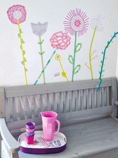 Hier sind Ihrer Fantasie keine Grenzen gesetzt! Die Blumen wurden frei Hand mit bunten Deko-Bändern an die Wand geklebt.