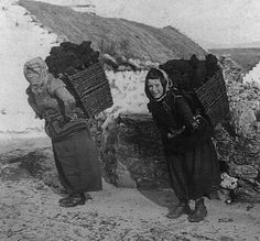 TURF'S UP, 1903  Achill Island, County Mayo, Ireland  This wonderful photo captures two young women carrying peat on their backs outside a white-washed, thatched cottage near Dooagh on Achill Island in 1903.